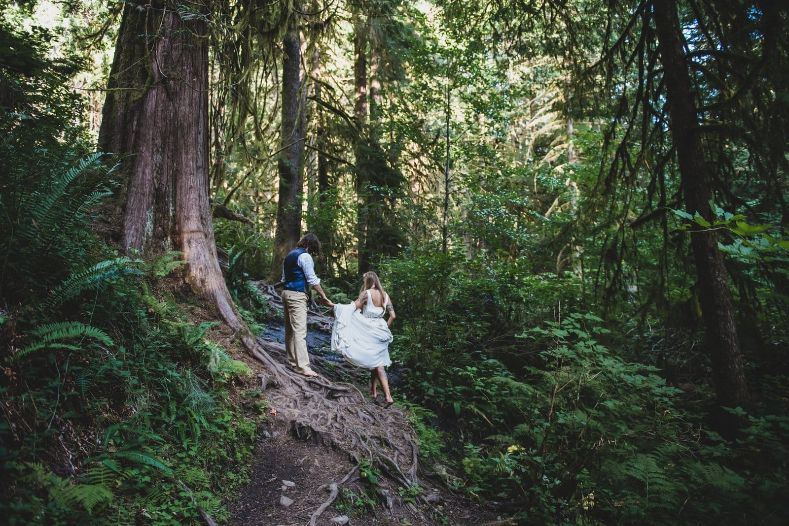 Bride and groom hike in forest.