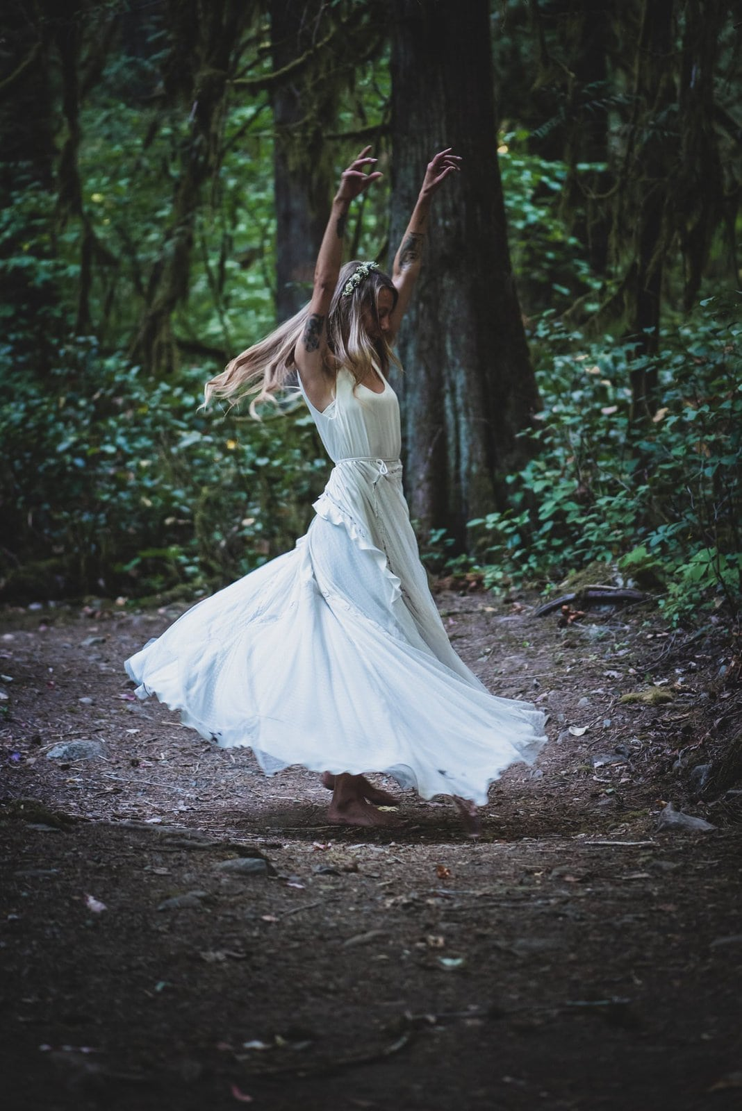 Detail shot of bride twirling in the forest.