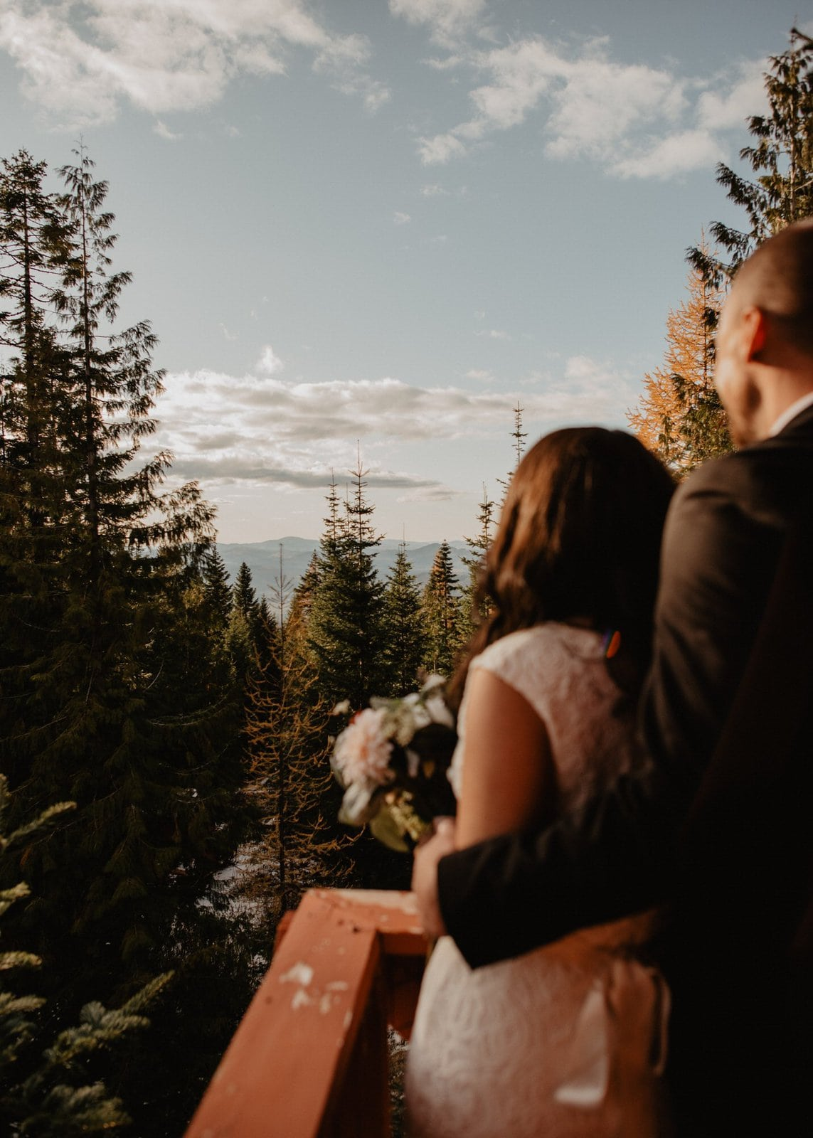 Bride and groom looking out to the mountainside.
