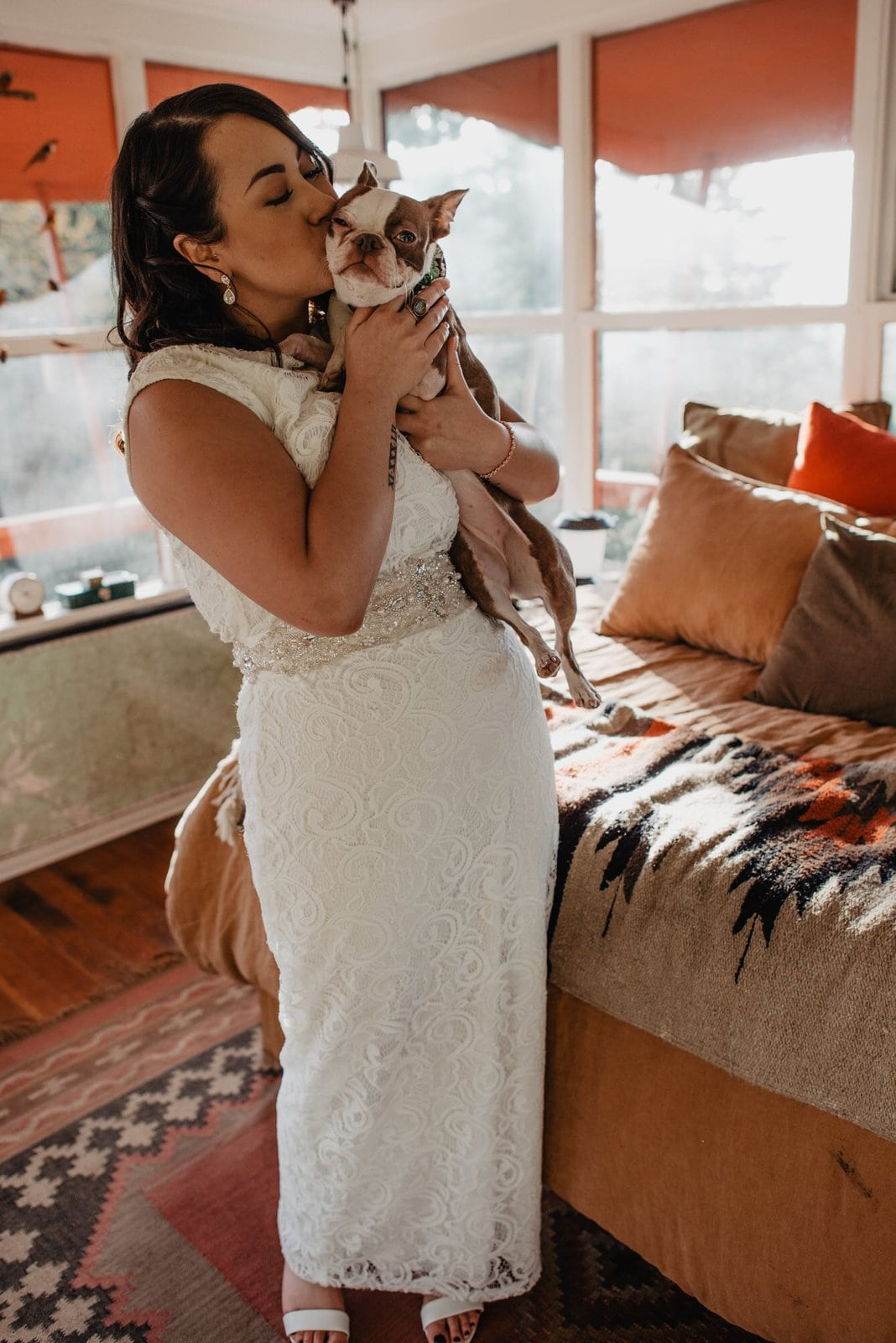 Bride hugs her dog during wedding.