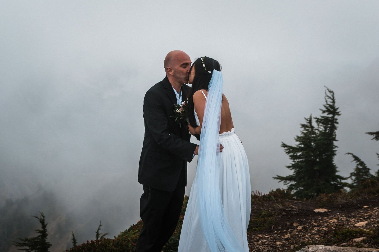 bride and groom share a kiss on the mountain.