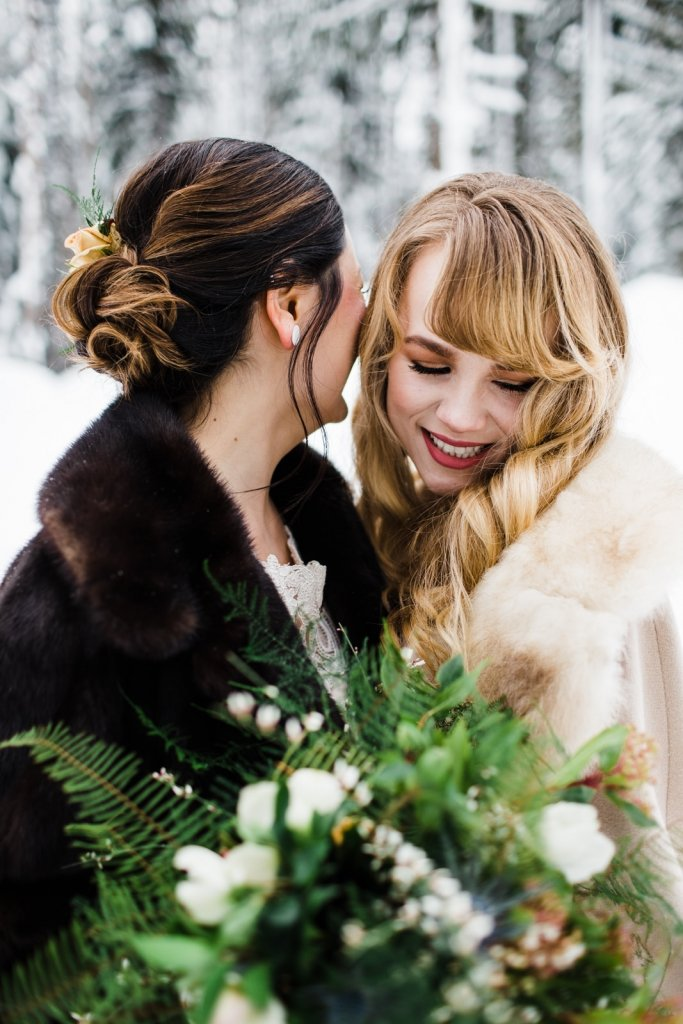 brides snuggle during winter wedding portraits.