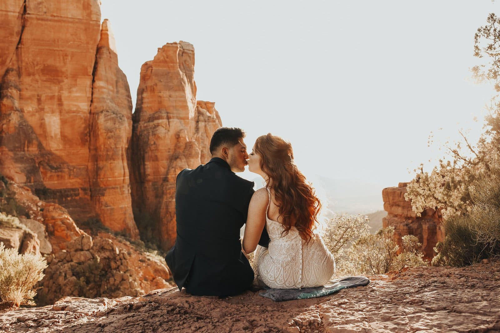 Couple shares a kiss at red rocks in Sedona.