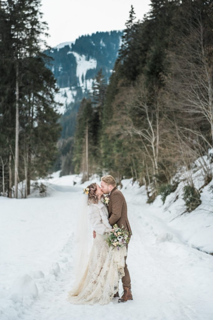 Bride and groom share a kiss for winter elopement.