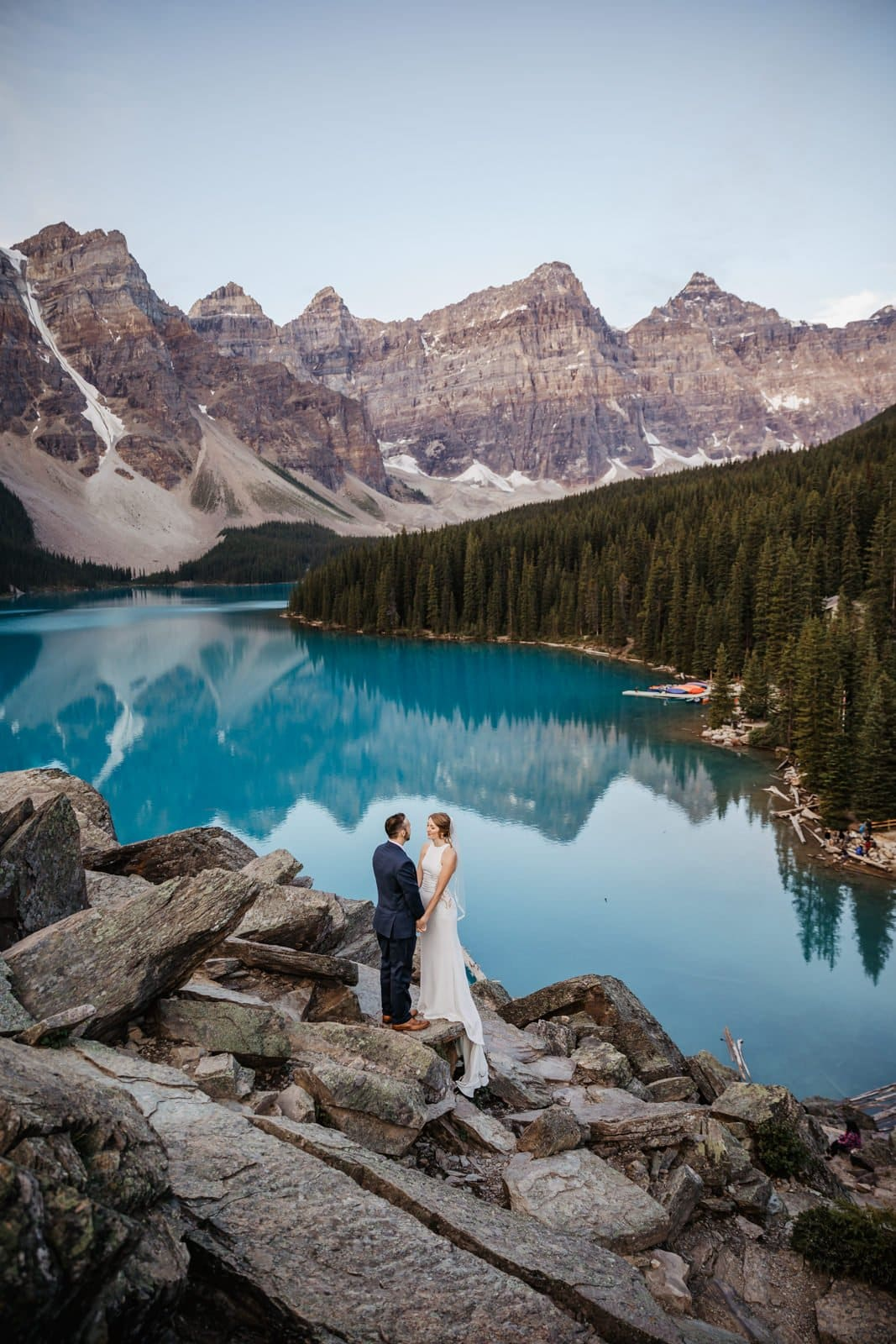 Couple standing next to pretty blue water in banff national park