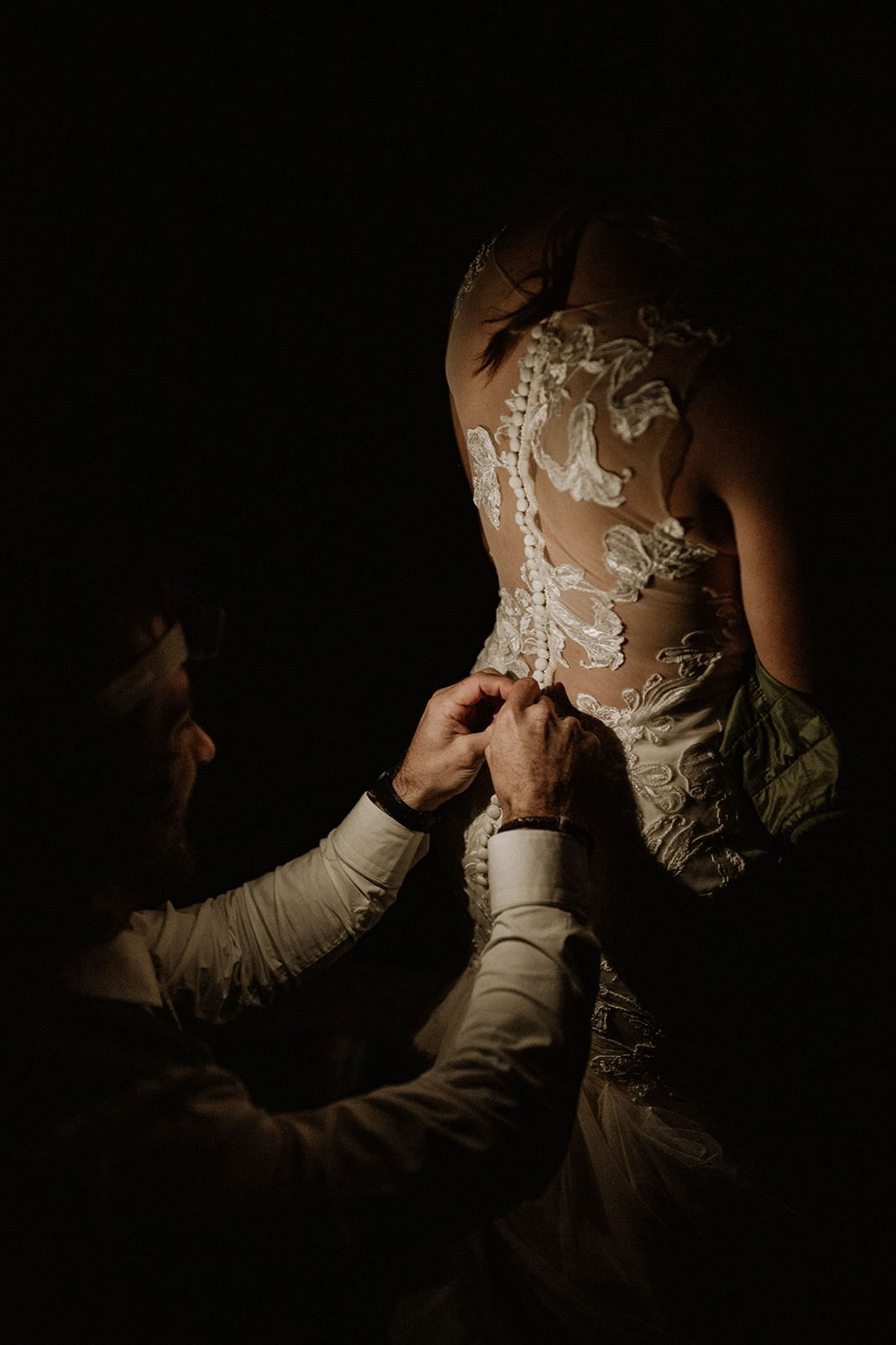 groom helping his bride get dressed