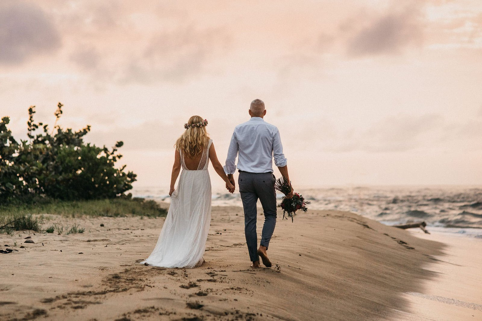 husband and wife walking on beach.