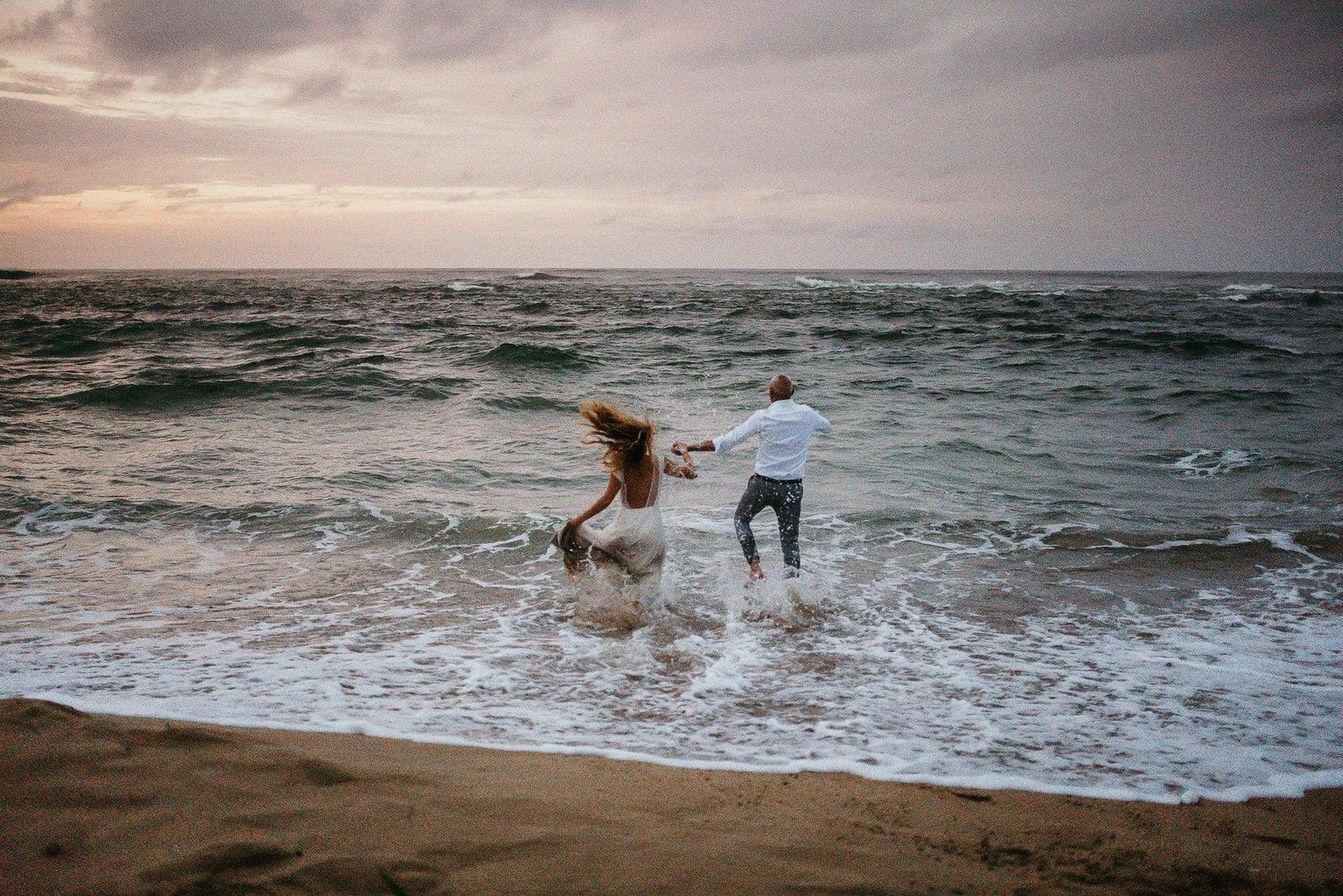 couple running into Costa Rica beach