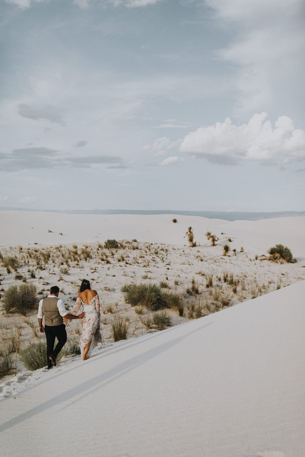 bride and groom walking in desert.