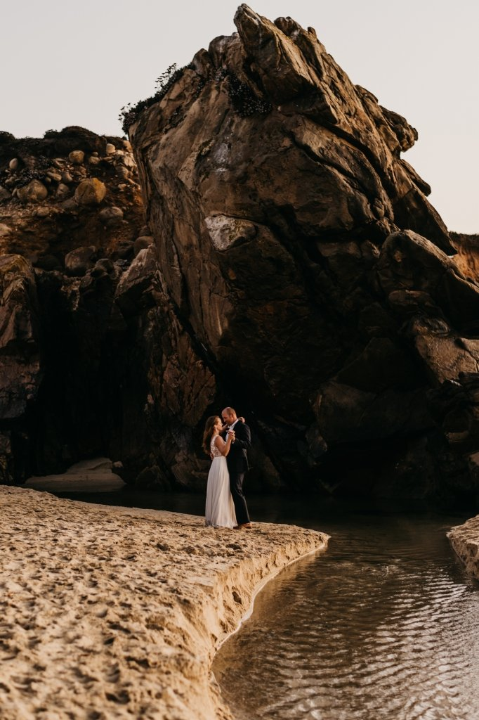 bride and groom by cave in California