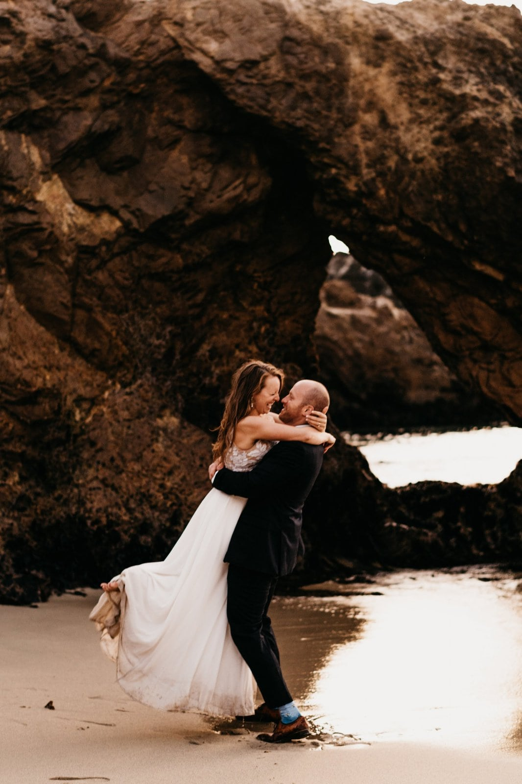 bride and groom by cave.