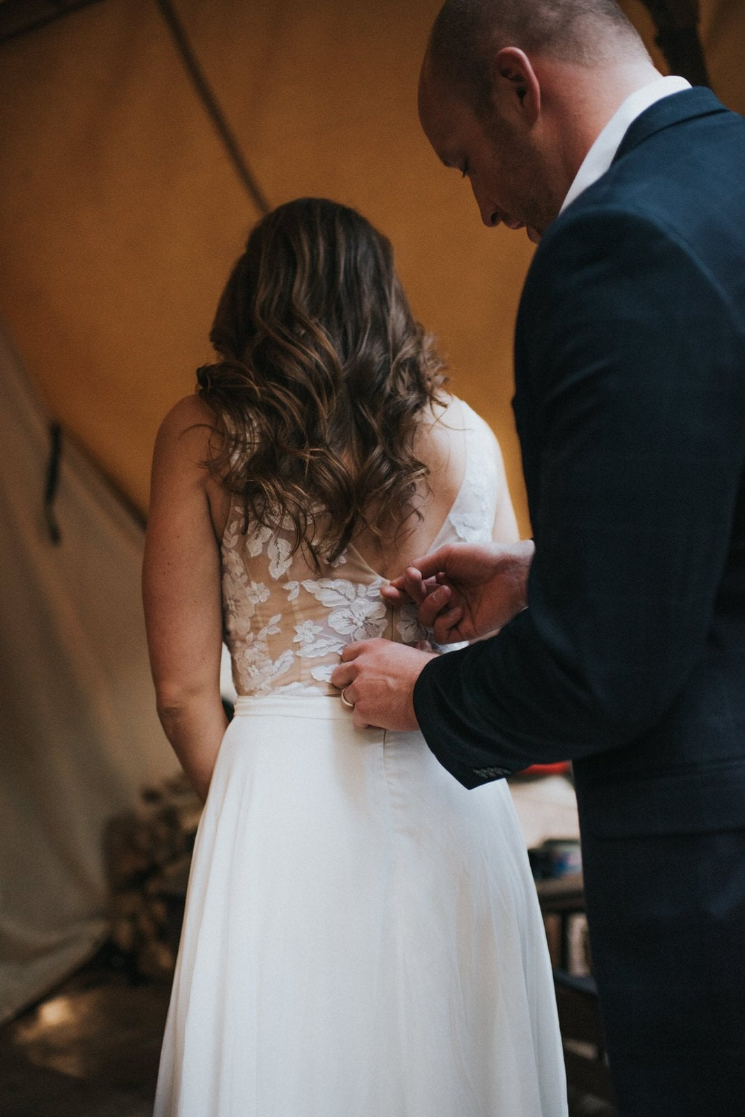 groom zipping wedding dress.