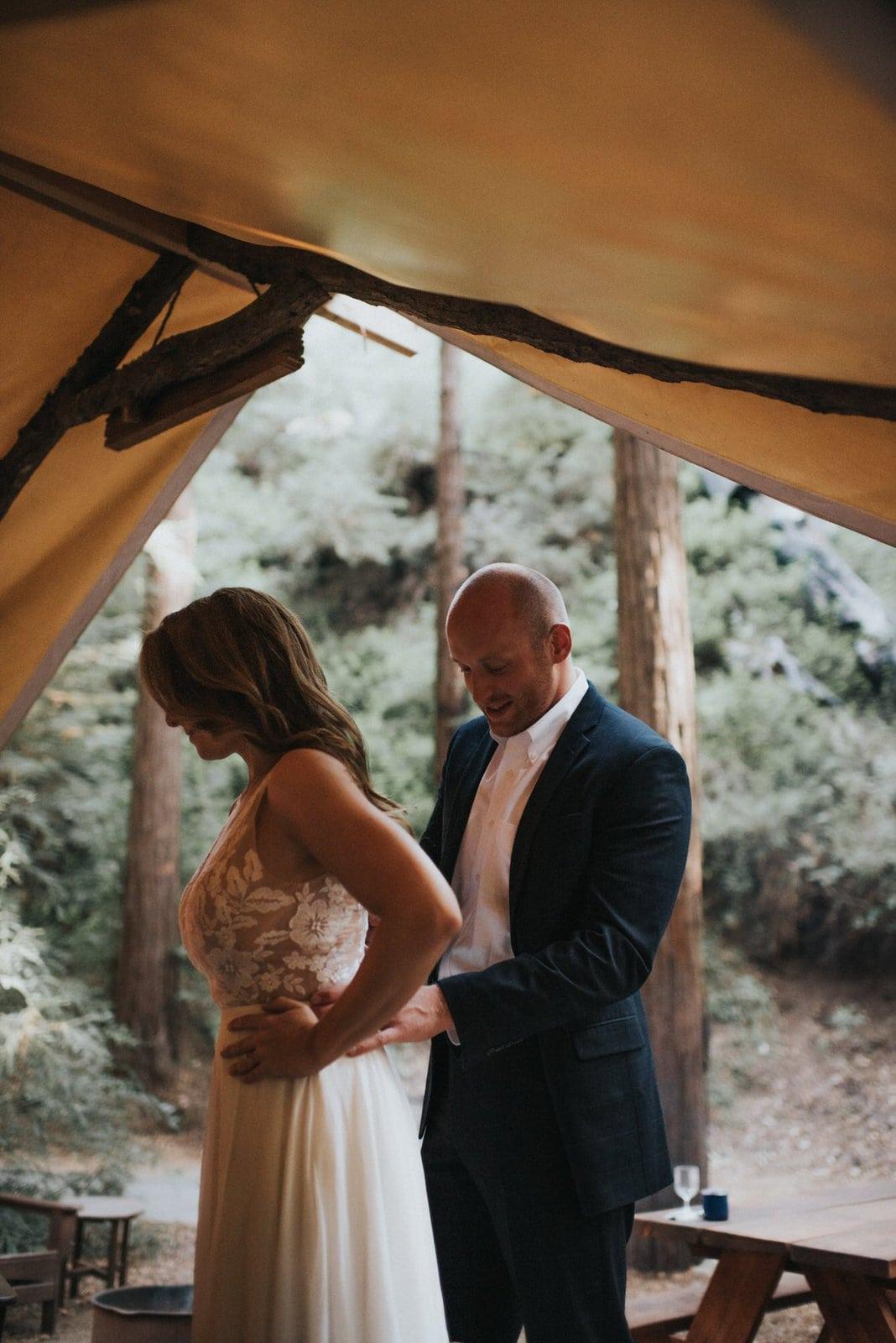 groom helping bride in wedding dress.