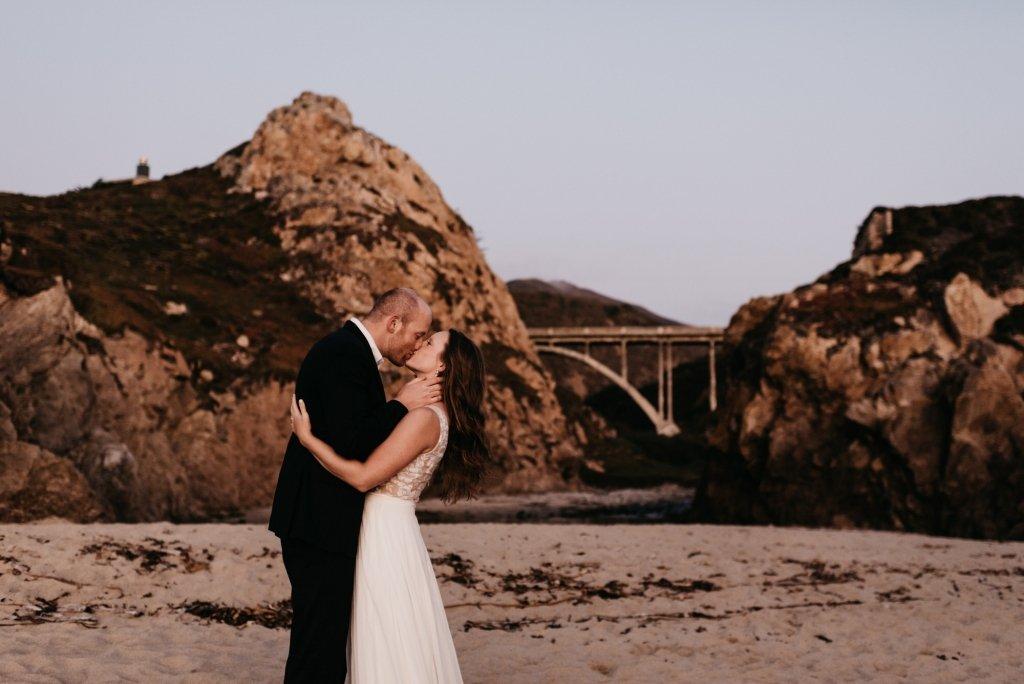 groom kisses his bride by California Big Sur