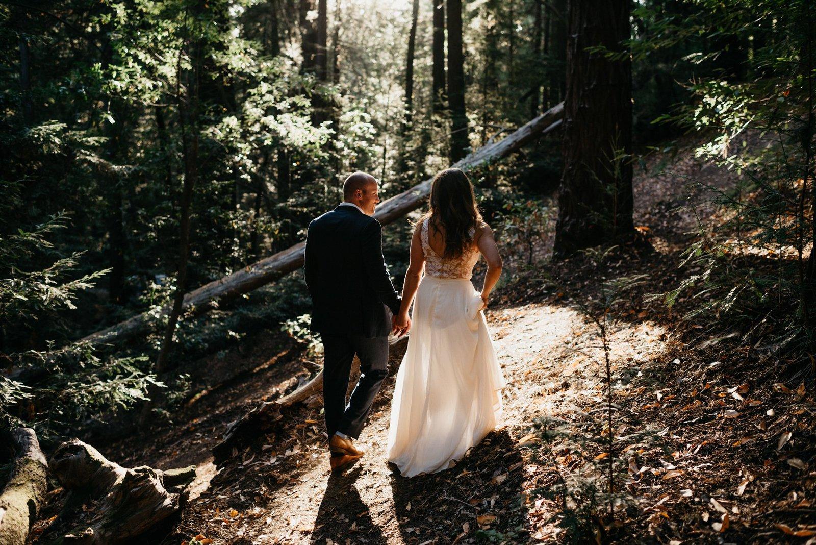 bride and groom walking in the redwoods