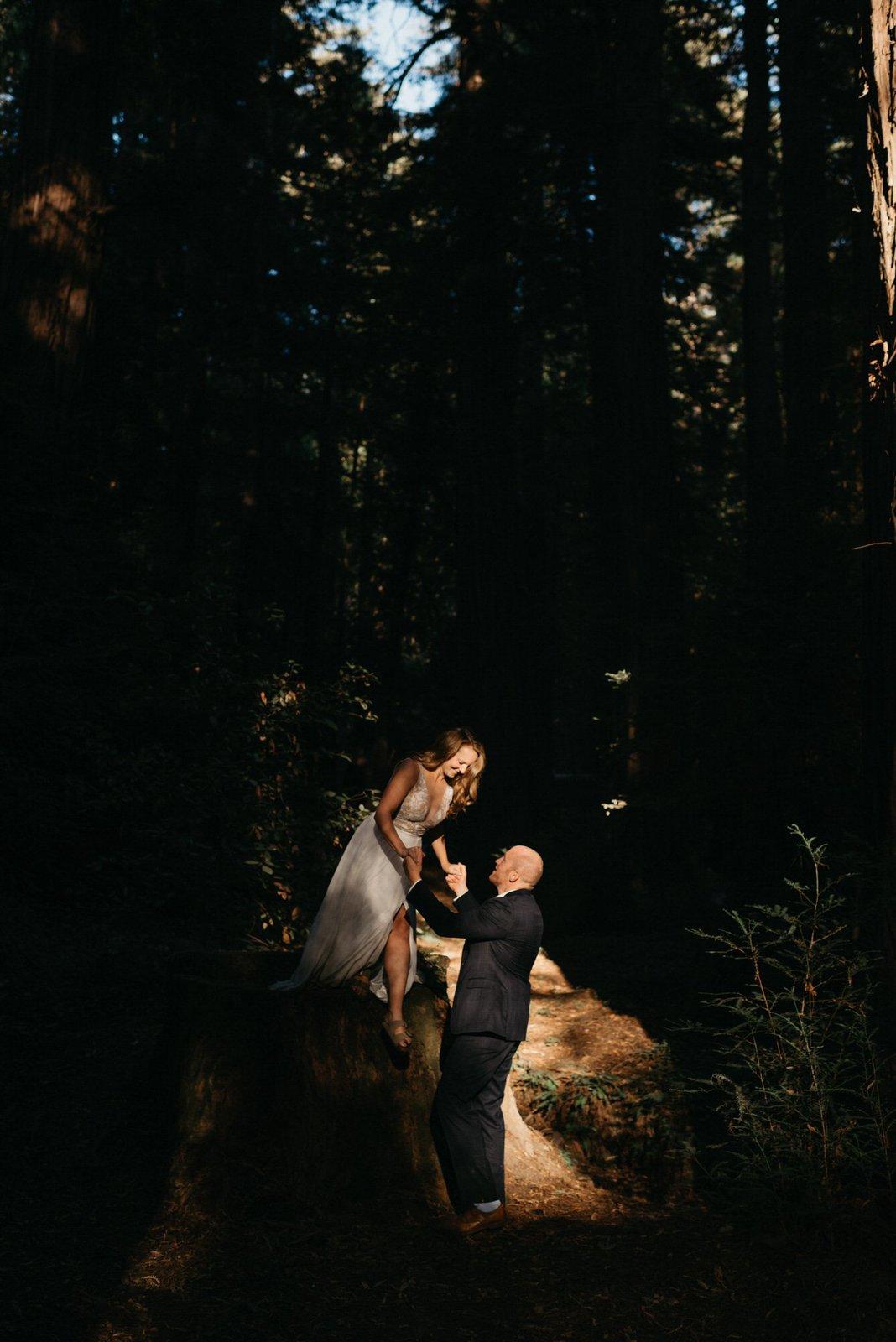 groom helping his bride in the Redwoods