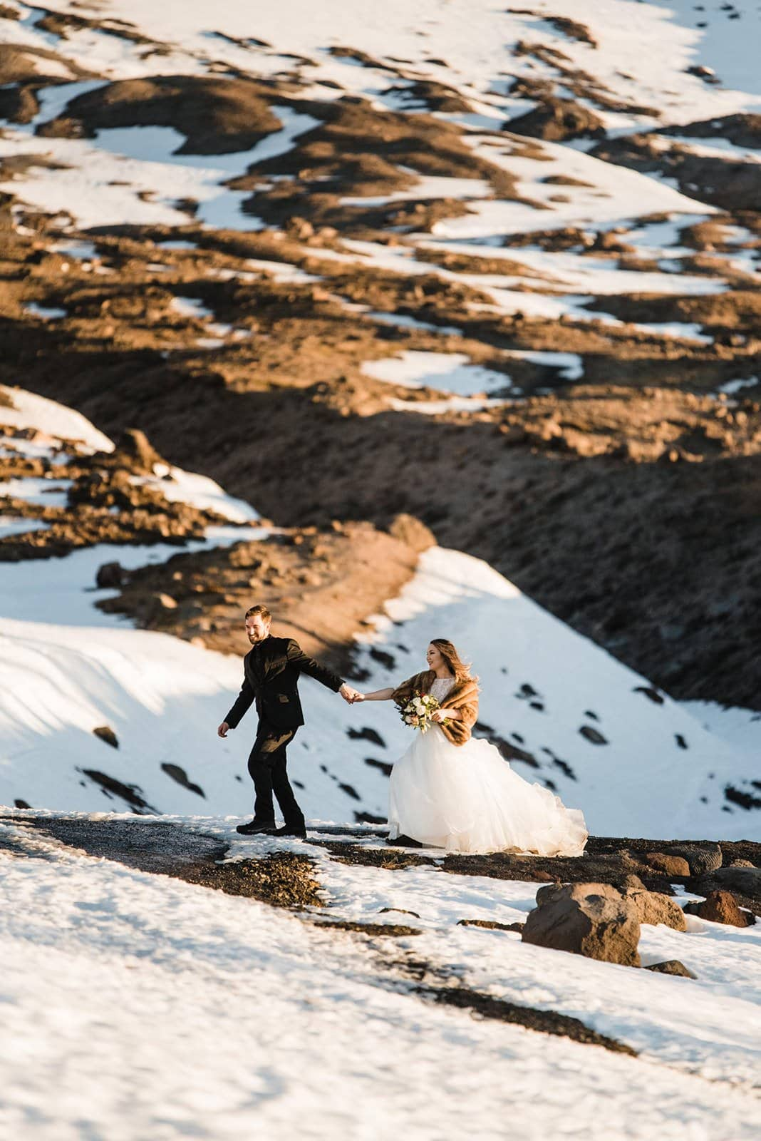 bride and groom walking through mountain