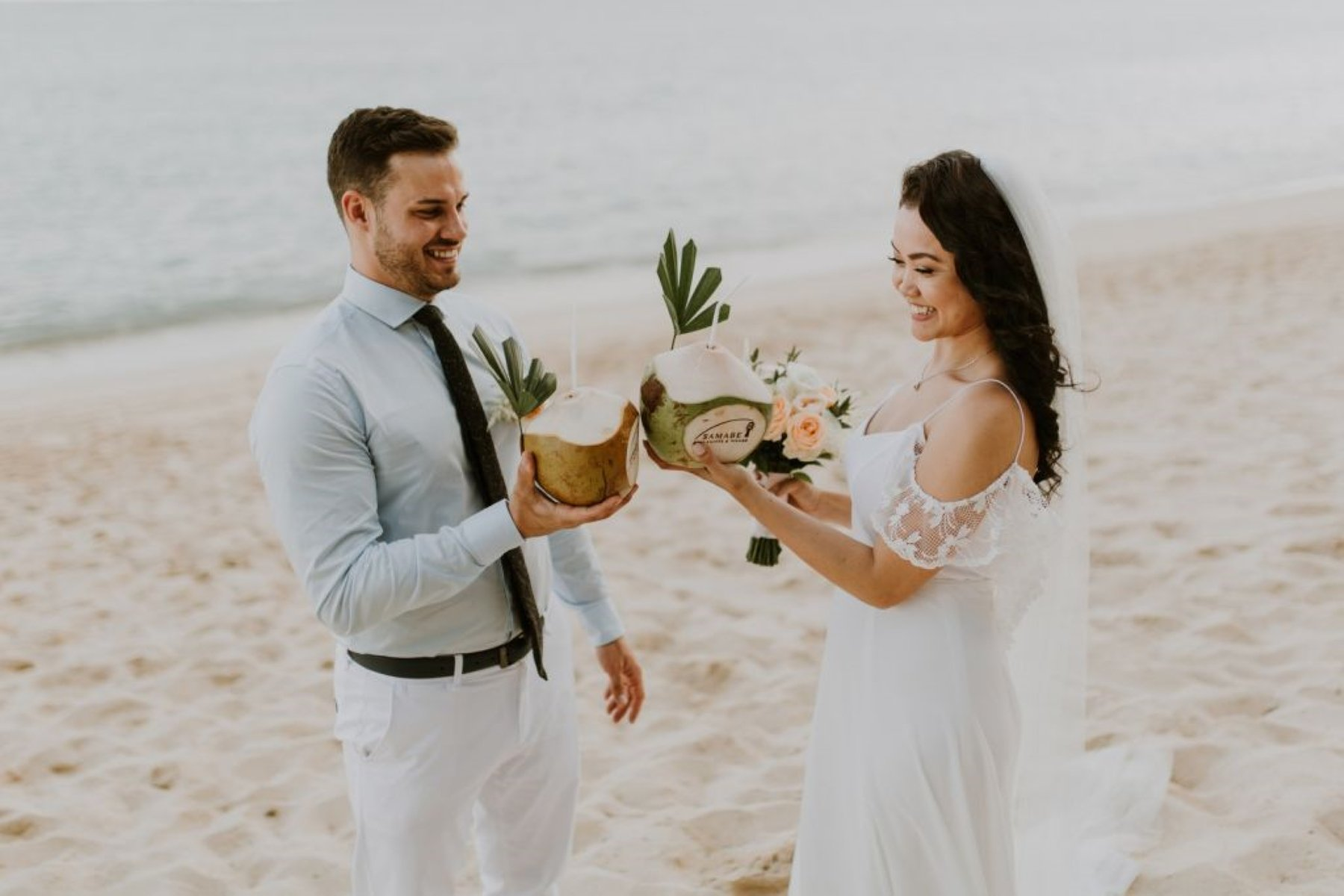 bride and groom cheers coconuts after bali elopement