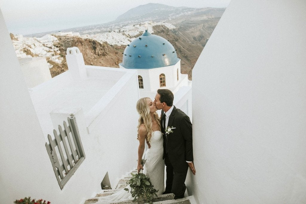 beautiful couple kissing int he streets of greece at best honeymoon destinations