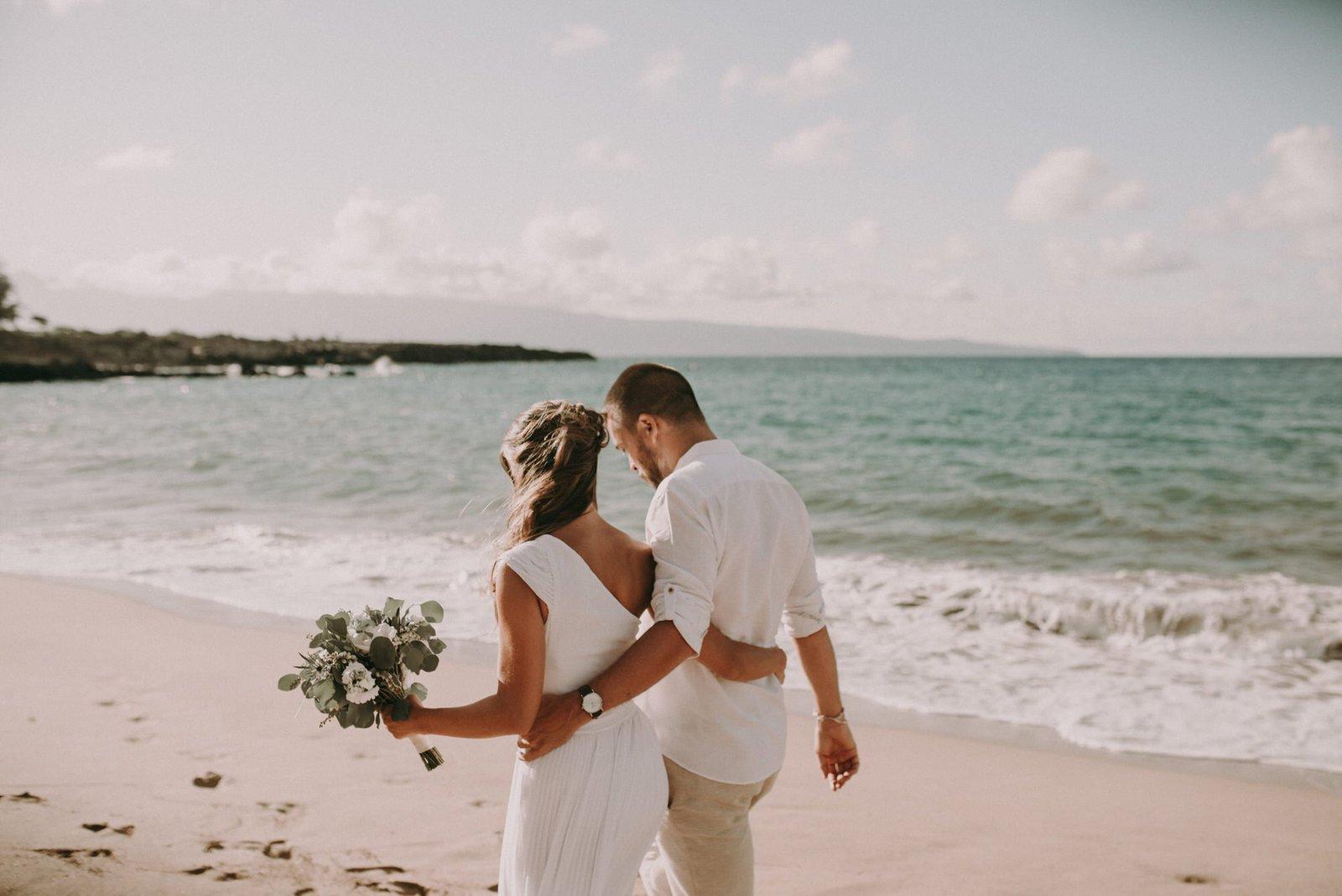 bride and groom walk in beach in Hawaii