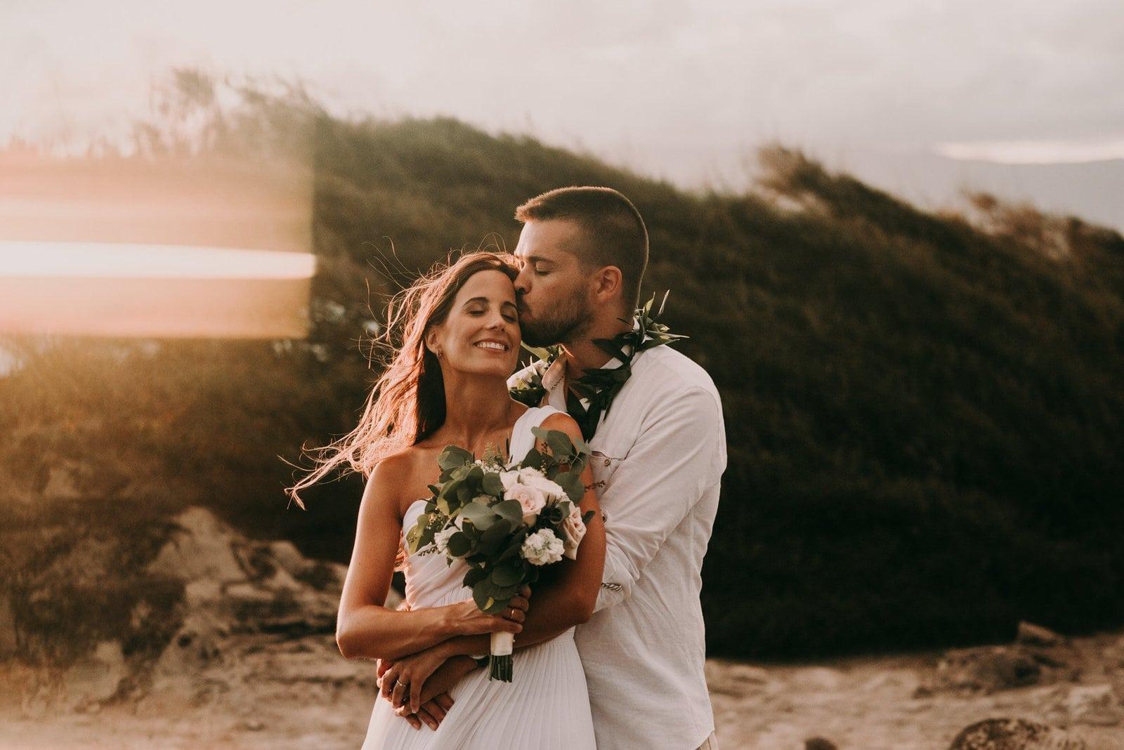 groom kisses his bride as sun sets