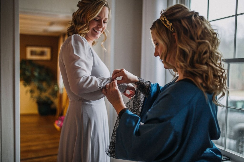 bride helping matron of honor get ready