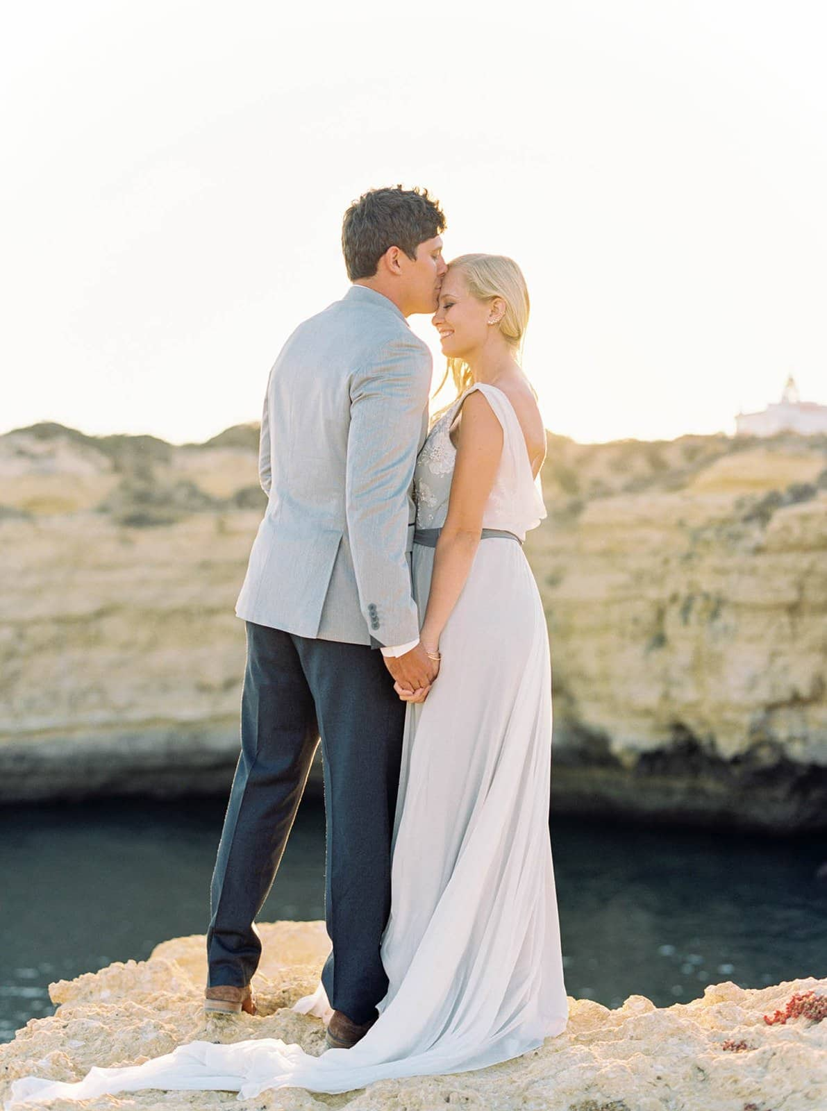 husband kissing wife on cliff