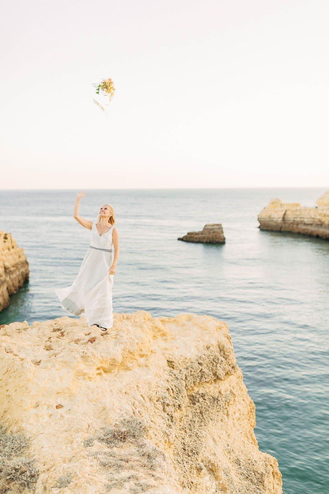 bride throwing her bouquet into the ocean