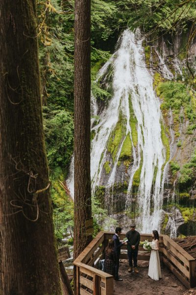 Sophie & Keven reading their vows under a Washington waterfall