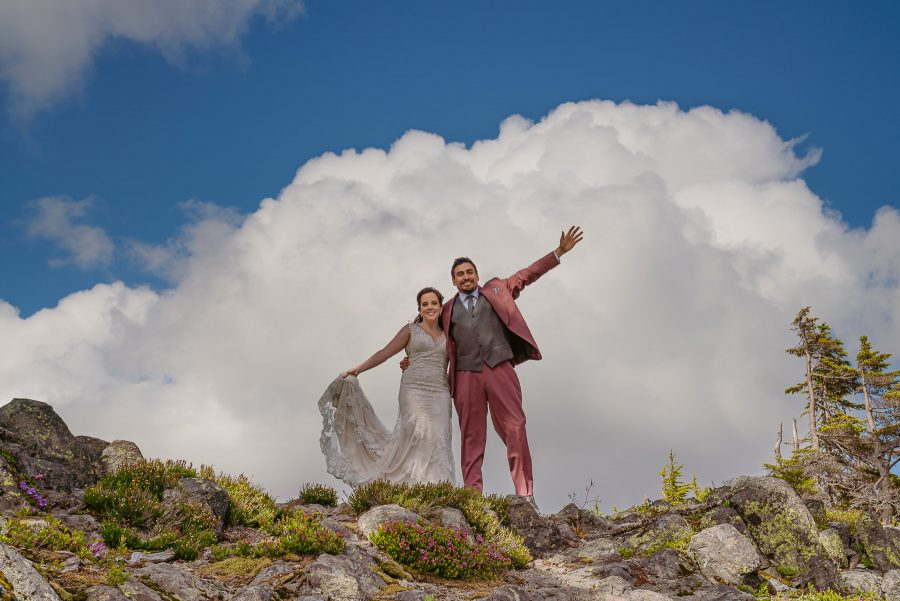 Couple stands on top of hill with blue sky and clouds behind them