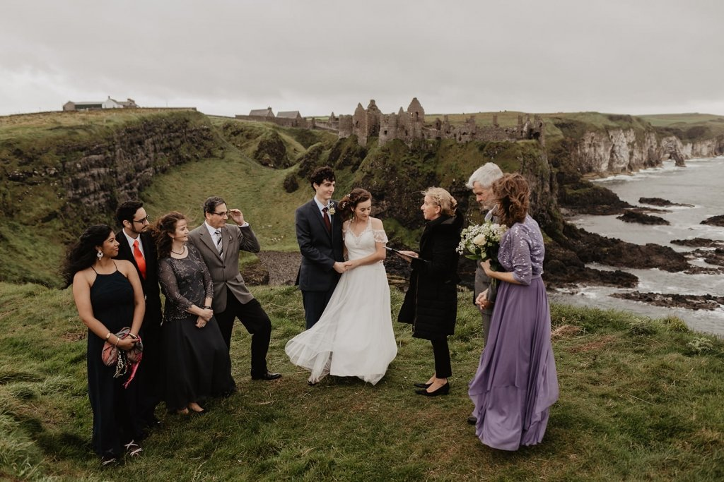 bride and groom with immediate family getting married in front of Dunluce Castle in Ireland.