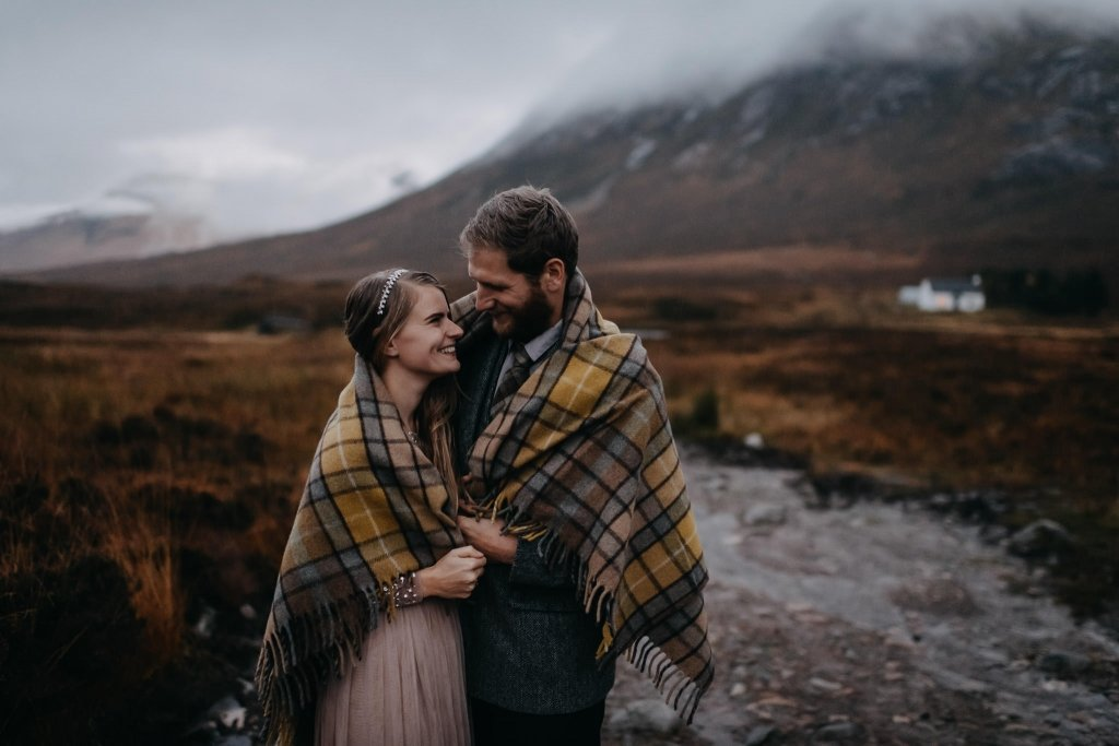 couple snuggling under blanket during their rainy engagement adventure in Glencoe after their handfasting ceremony together.