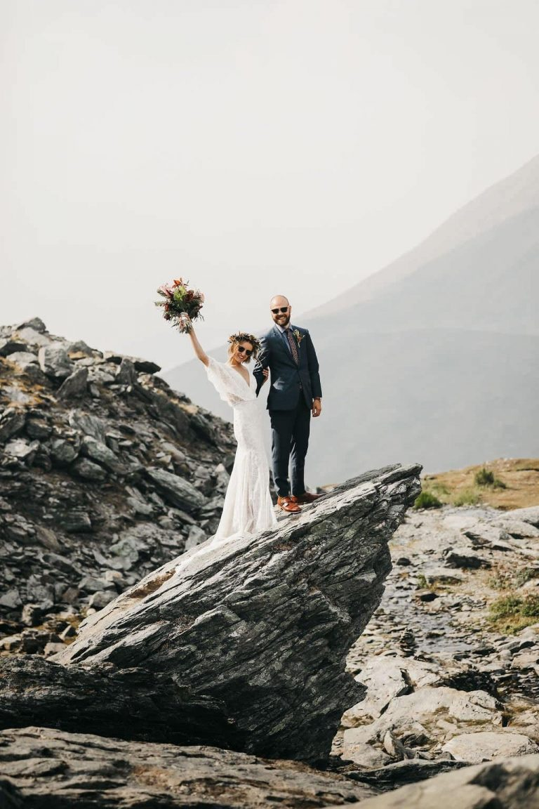 bride raising her bouquet up in the air after their Alaska wedding ceremony