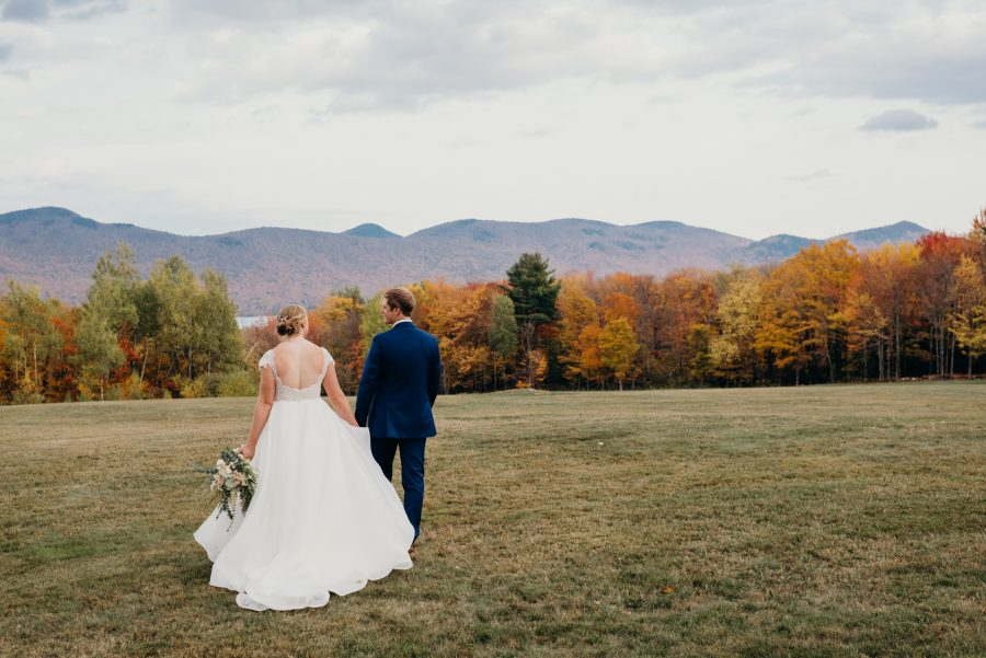 bride and groom holding hands looking out at the green mountains during their Vermont Mountain Top Inn wedding