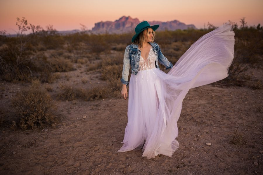 country western bride in cowboy hat in front of the superstition mountains