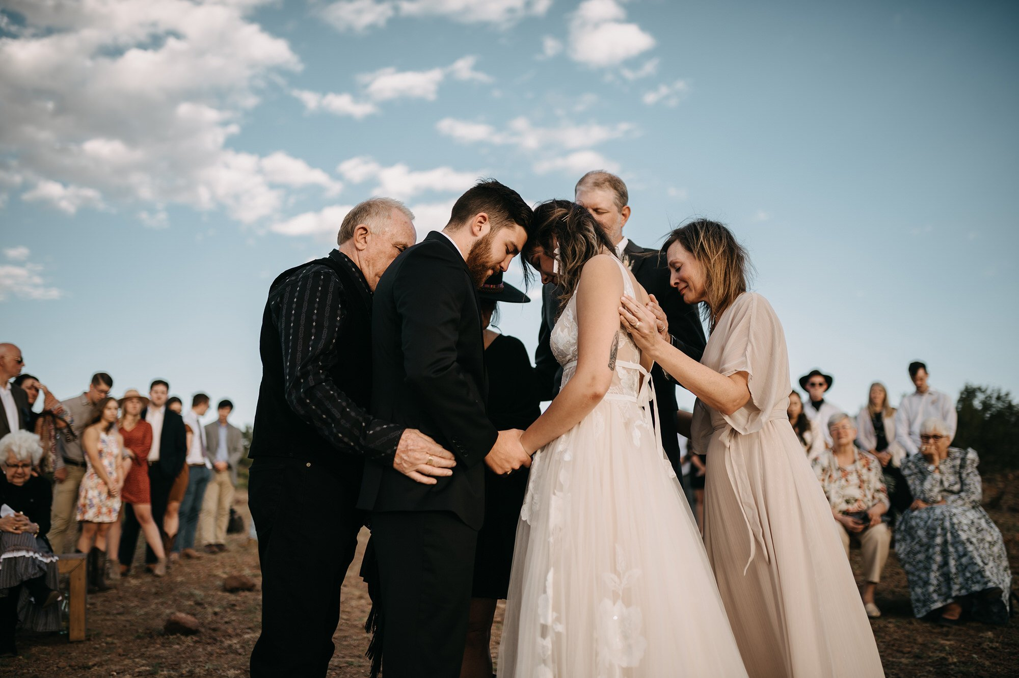 family praying with bride and groom during ceremony in Texas