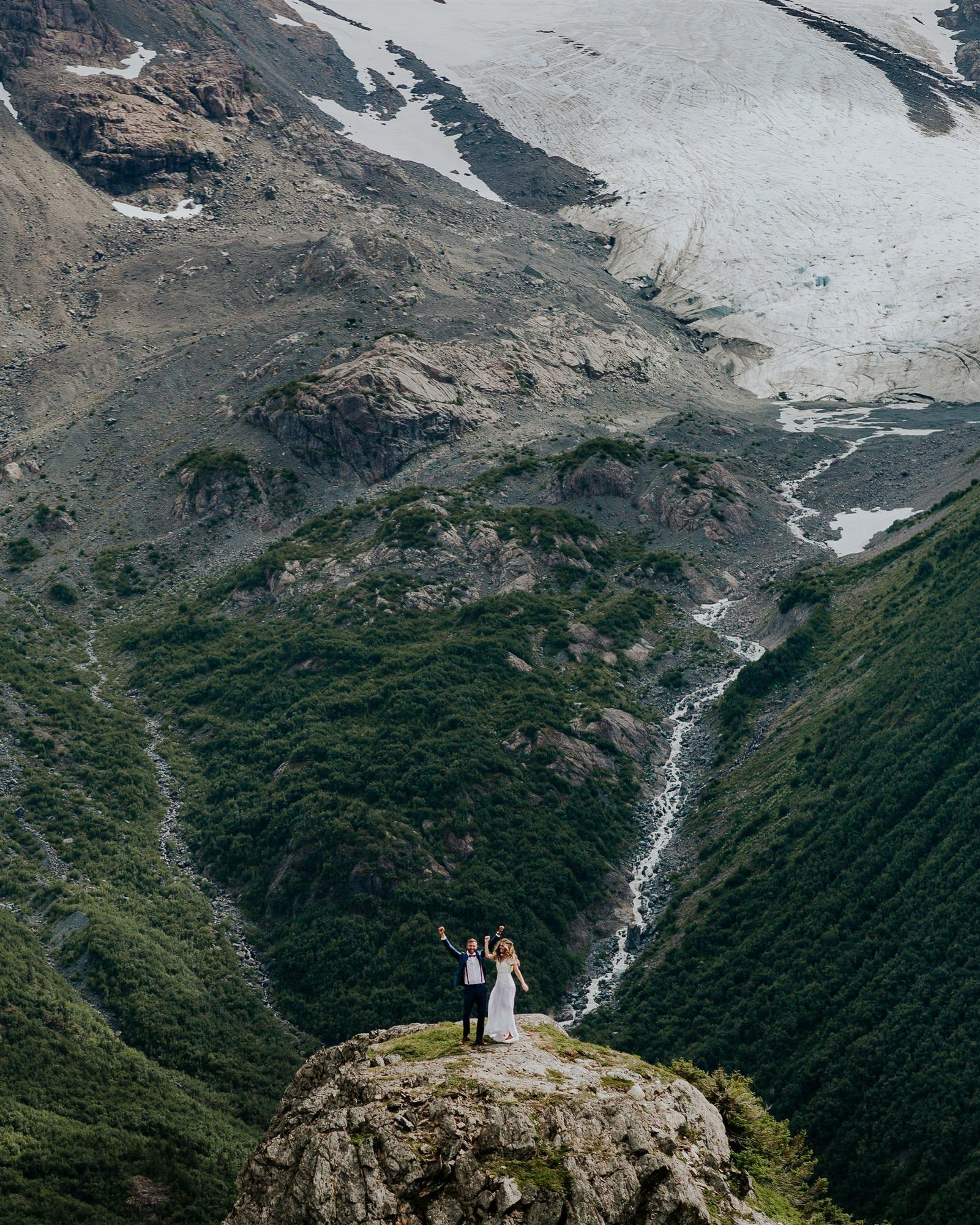 couple standing on the top of a mountain in Alaska from their helicopter adventure