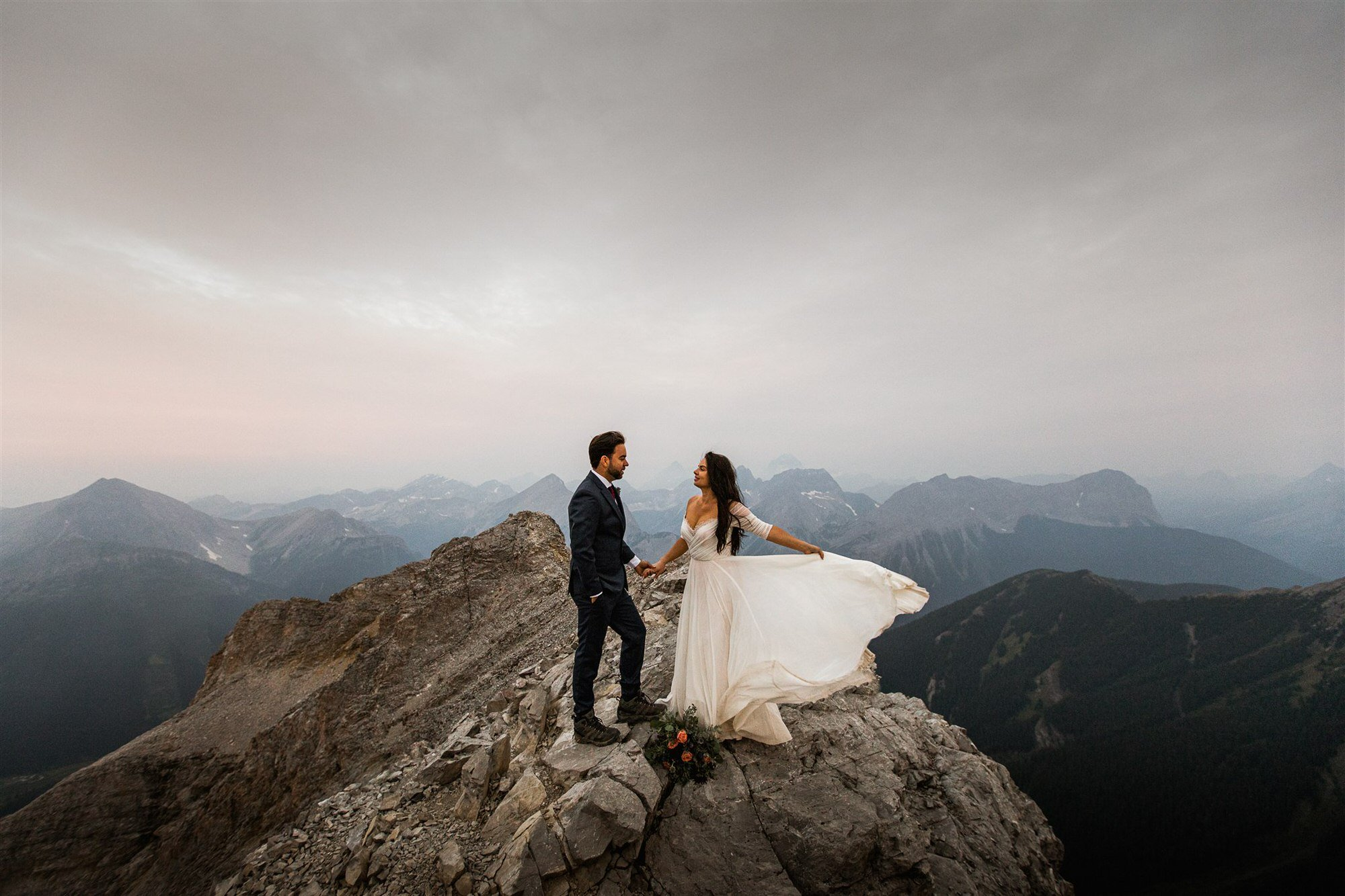 elopement photography in Banff of couple on a cliff and bride's elopement dress in the wind