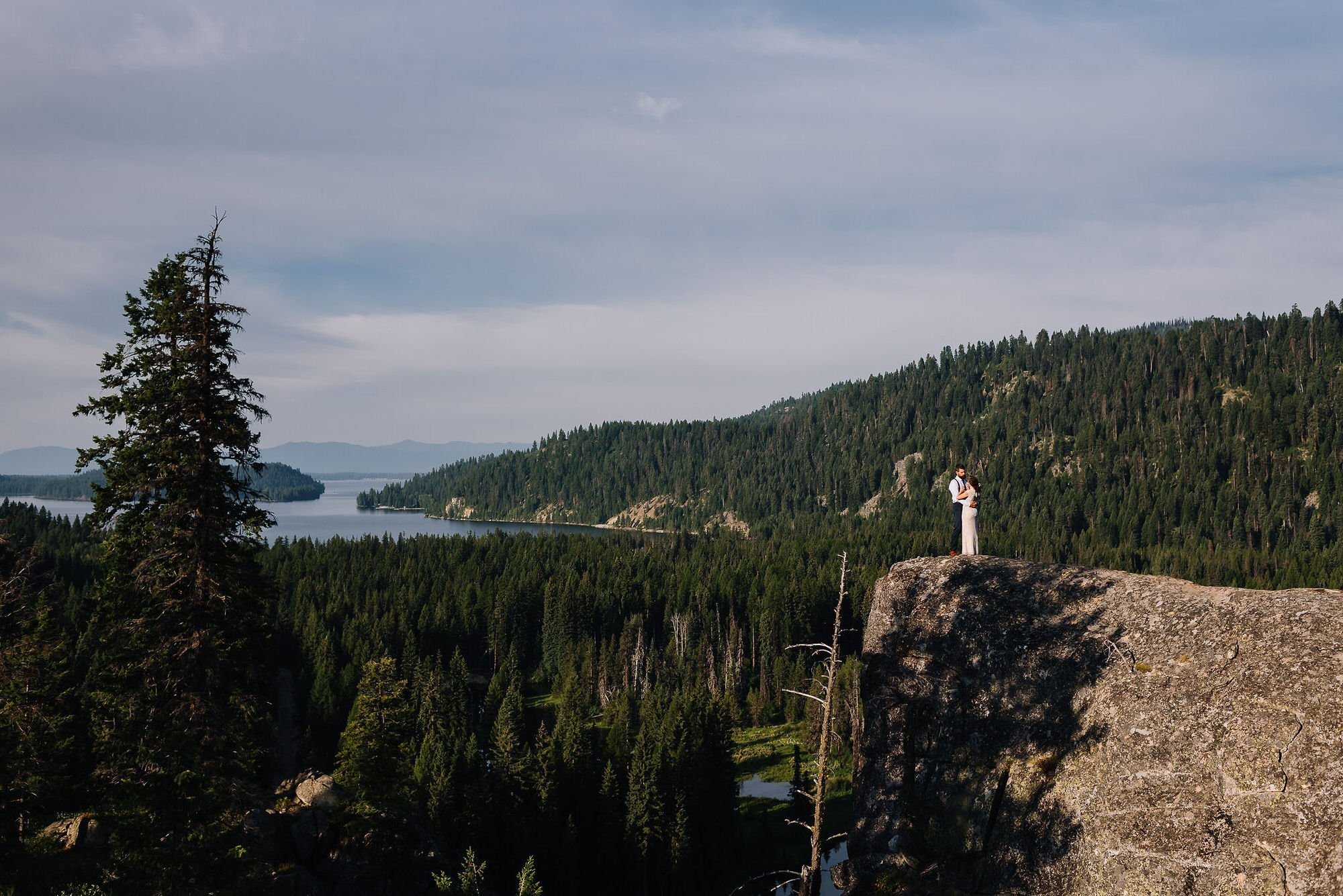 McCall Idaho elopement with a forest view and a couple standing by the edge with a lake view