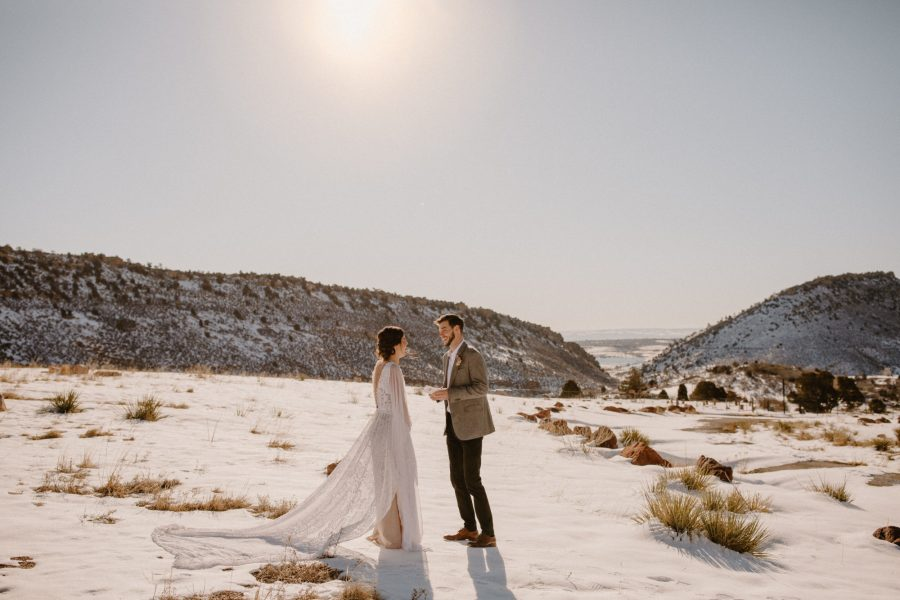 Bride and groom sharing vows at sunrise at Red Rocks Park in Morrison, CO.