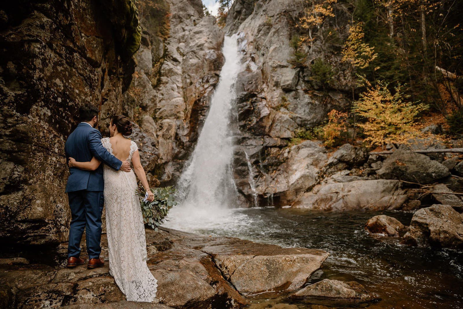 couple at a waterfall within the white mountains trails in NH