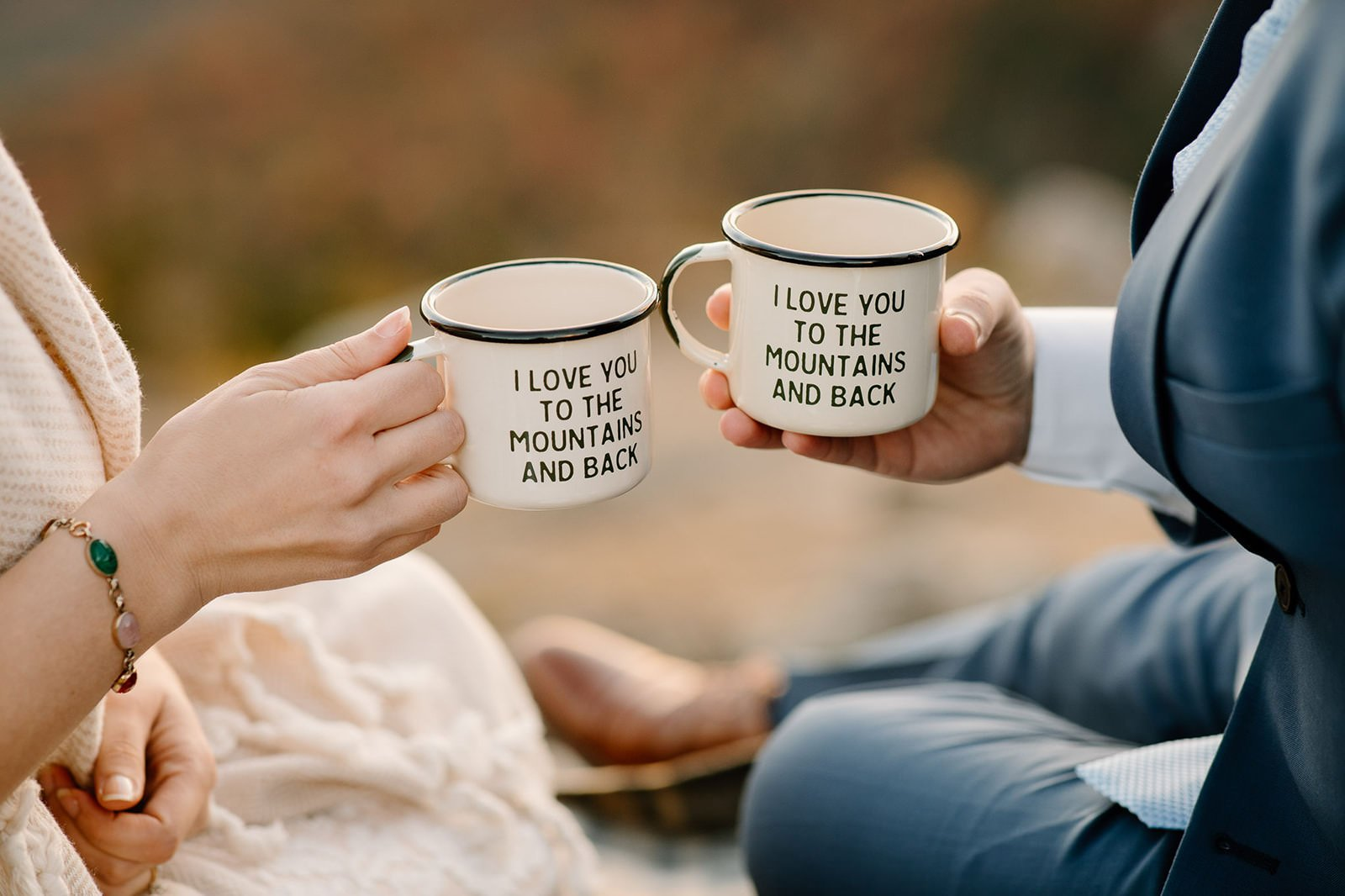 Couple holding custom wedding mugs during their elopement picnic