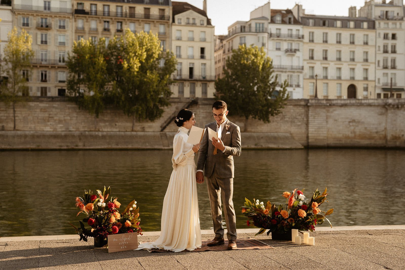 reading personal vows to each other during elopement by Seine River in Paris, France